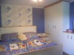 Blick in ein komplett nach Mass angefertigtes Schlafzimmer im friesichen Stil in blau und weiss mit buche Akzenten .