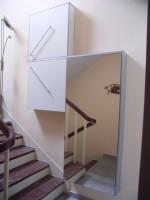 Blick auf einen Schuhschrank mit geringer Tiefe, der parallel zur Treppe im Treppenhaus montiert wurde.