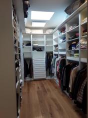 in eine komplett mit Regalen , Stangen und Auszügen ausgebaute Ankleide