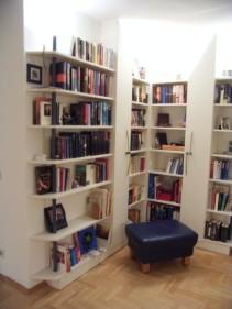 Blick in eine mit Bücherregelen und zwei Schränken mit je einer Tür nach Mass  ausgestattete Raumecke. Es wurde indirekte Beleuchtung installiert, die den Raum über Deckenreflex weich beleuchtet.