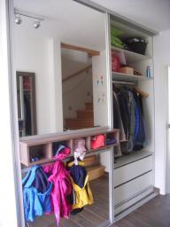 Blick in die Diele eines Einfamilienhauses. Sie wurde mit einem Garderobeneinbauschrank nach Mass ausgebaut der sowohl einen verspiegelten Schuhschrank, ein Schubladenelement, ein Kleiderschrankelelme