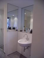 Blick in eine linke Badecke, die mit einem , den vorhandenen Spiegel perfekt ergänzenden teilverspiegelten Schrank nach Mass ausgebaut wurde.